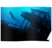 Scuba Diver shining torch by shipwreck Poster