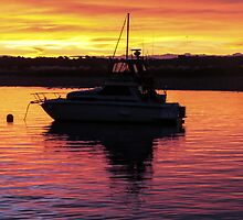 anchored launch in the sunset by Anne Scantlebury