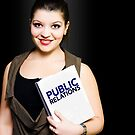 Smiling woman with public relations folder by Ryan Jorgensen