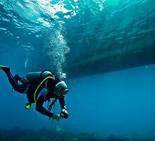 scuba diver under a boat by paulcowell