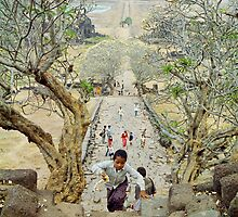 Flower girl on the steps of Wat Phu temple, Laos. by Phil Bower
