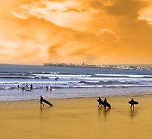 young surfers walking on sunset beach by morrbyte