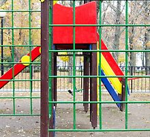 Empty children's playground and a slide in the park by vladromensky