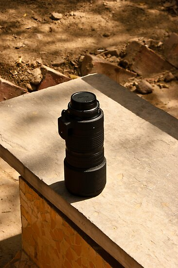 Nikon zoom lens on a stone bench by ashishagarwal74