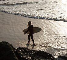 Surfer walking on beach at sunset by Pat Garret