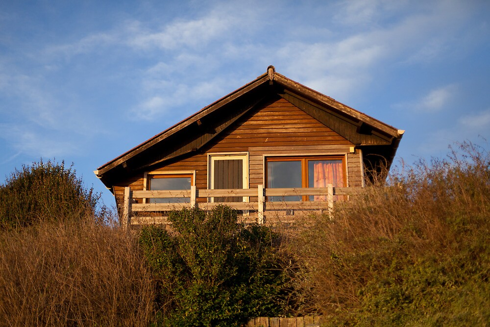 wooden house on a grassy dune by Pat Garret