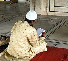 A pious devotee reading the Quran inside the Jama Masjid in Delhi by ashishagarwal74