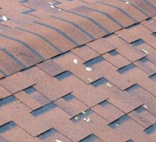 Top view of brown roof shingles with a few fallen leaves Sticker