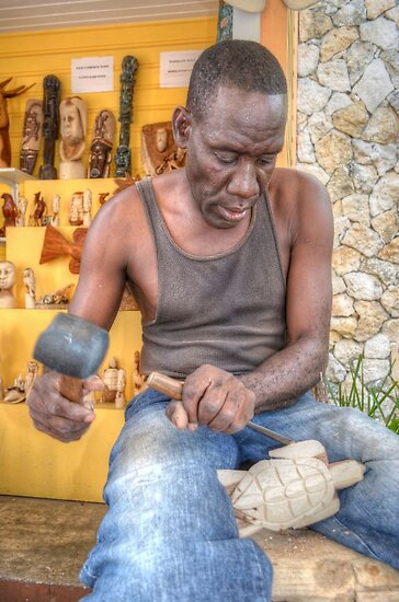 Bahamian Sculptor carving the Wood at the Straw Market in Nassau by 242Digital