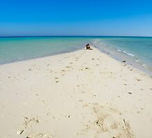 woman sits alone on a stretch of deserted beach  by PhotoStock-Isra