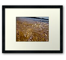 Close up of bubbling sea water on beach with sunlight sparkles Framed Print