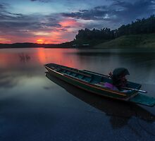 wood Boat in sunset at Sirikit Dam by arthit somsakul
