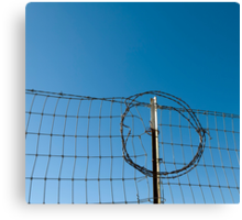 Section of a fence topped by barbed wire Canvas Print
