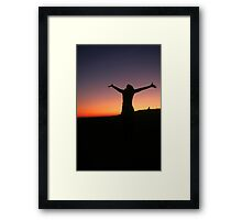 Silhouette of an exited woman at sunset Framed Print