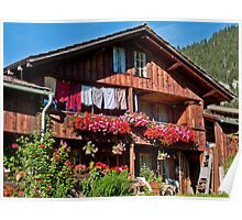 Red geraniums and laundry in an old wooden farmhouse in Grindelwald Poster