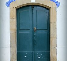 Green door with decorative azulejos above by juliedawnfox