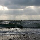 Surfers in winter with rays of sunlight, Wembury, near Plymouth, Devon, UK by silverportpics