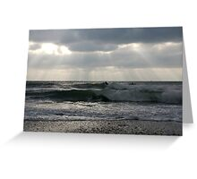 Surfers in winter with rays of sunlight, Wembury, near Plymouth, Devon, UK Greeting Card