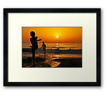 children playing on the Beach at sunset Framed Print