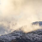 Sunlit clouds over mountain. by Skipnes