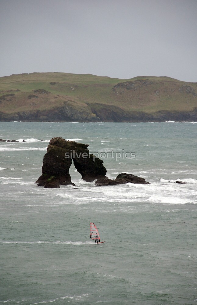 Windsurfer in stormy weather passes Thurlestone Rock, Devon, UK by silverportpics
