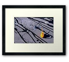 Orange watering can on hot asphalt Framed Print