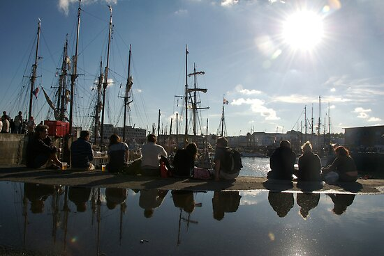 People relaxing on the harbourside with tall ships masts behind, Brest 2008 maritime festival, France by silverportpics