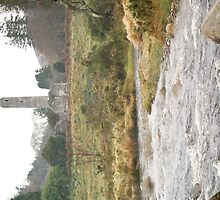 Glendalough Round Tower with river by DES PALMER
