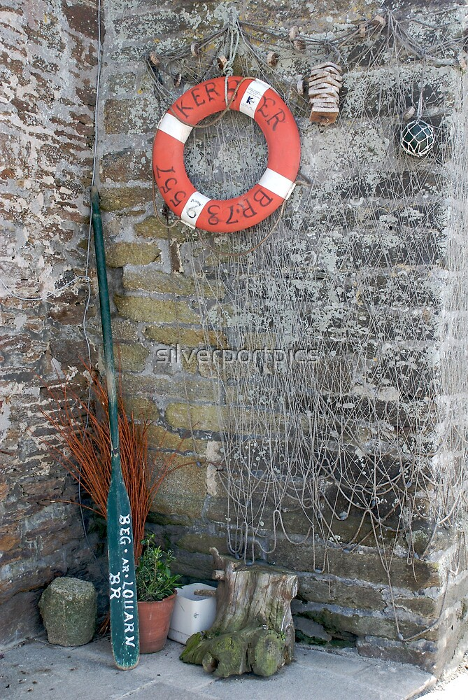 Lifebuoy, boat oar and fishing nets outside house Le Conquet, Brittany, France by silverportpics