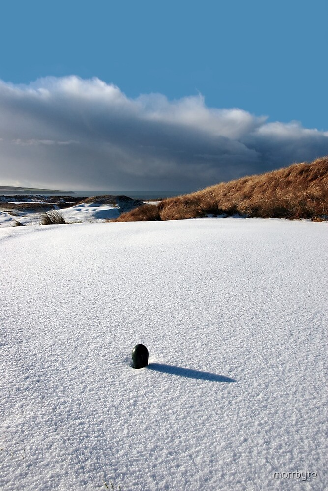 green golf tee on snow covered golf course by morrbyte