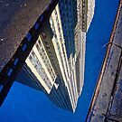 Empire State Building reflected in puddle by Daniel Sorine