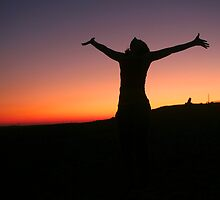 Silhouette of an exited woman at sunset by PhotoStock-Isra