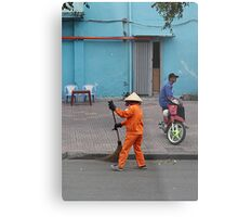 woman sweeps, man minds his bike.  Metal Print