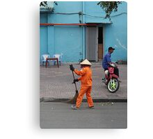 woman sweeps, man minds his bike.  Canvas Print