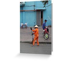 woman sweeps, man minds his bike.  Greeting Card