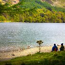 Two walkers share a view of Lake Buttermere, UK by Elana Bailey