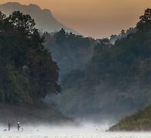 Fisherman rowing a boat through misty river by goldsaintphoto