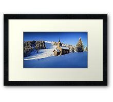 Winter chapel on the hill in the Alps Framed Print