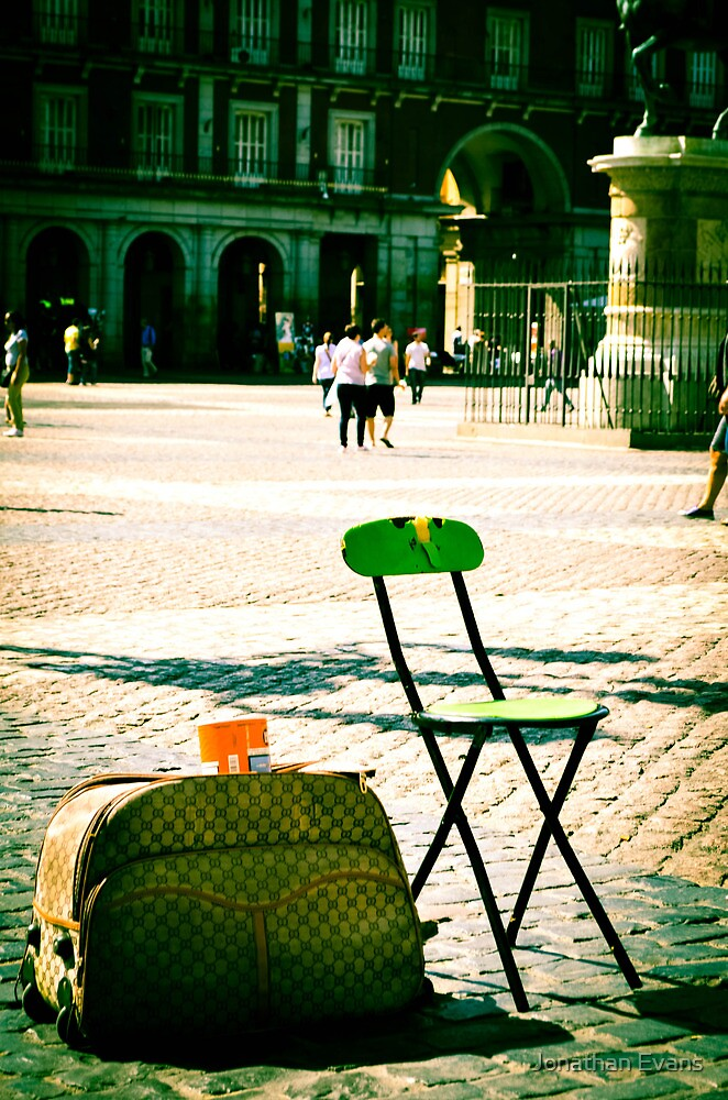 An empty chair in a big plaza by Jonathan Evans