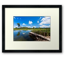 Wetland pond and wooden bridge in a clear sky Framed Print