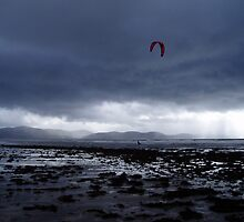 Atlantic storm approaches as man with hand glider on Inch Beach. by Grace Johnson