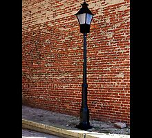 Antique Street Light Against Red Brick Wall - West Main Street, Riverhead New York by © Sophie W. Smith