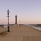 Sunrise over twin lighthouses Whitby. by Lilian Marshall
