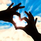 Silhouette hands in heart shape and blue sky by gianliguori