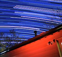 Galaxy Star Trails Pass Over Red Cabin Roof by Gavin Heffernan