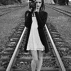 The girl with a Polaroid camera on a train track by Lissie E J