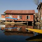 Yellow shikara in front of a run down area of houses in the Dal Lake in Srinagar by ashishagarwal74