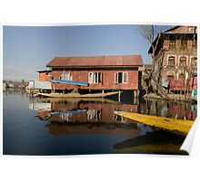 Yellow shikara in front of a run down area of houses in the Dal Lake in Srinagar Poster