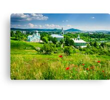 red poppy flowers and the green monastery Canvas Print