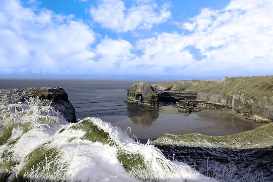 frosty snowcovered coastal beach view and virgin rock by morrbyte